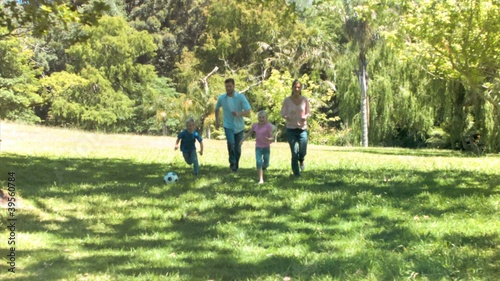 Family in slow motion running with a soccer ball