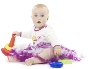 The little girl sits with toys on a white background