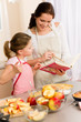Mother and daughter look baking cookbook