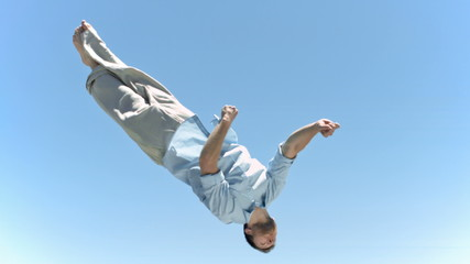 Young man jumping in slow motion while making a twist