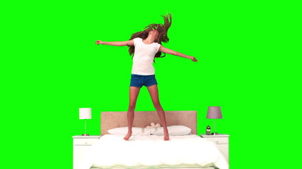 Woman jumping on her bed in slow motion