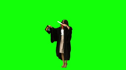 Graduated student in slow motion throwing her hat