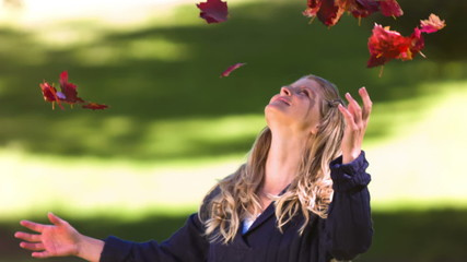 Blonde woman throwing leaves in slow motion