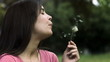 Woman blowing a dandelion in slow motion