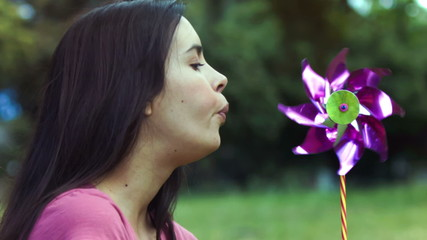 Woman breathing on a pinwheel in slow motion
