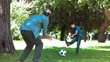 Boy playing soccer in slow motion with his father