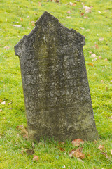 A tombstone on an old graveyard