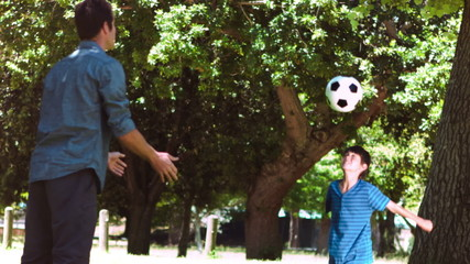 Boy playing soccer in slow motion with an adult