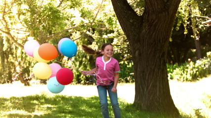Girl jumping in slow motion with balloons