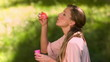 Woman blowing bubbles in slow motion