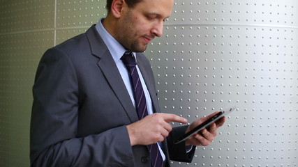 Businessman with tablet computer standing by the wall
