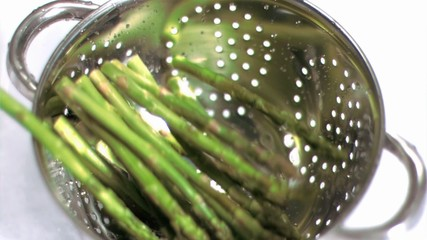 Asparagus falling into sieve in super slow motion
