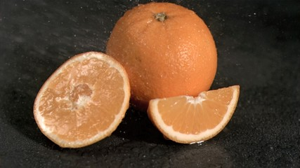 Water falling on oranges in super slow motion