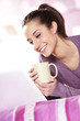 pretty girl smiles at the laptop with a cup of coffee in hand