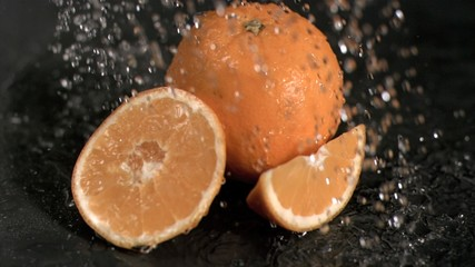Water raining in super slow motion on oranges