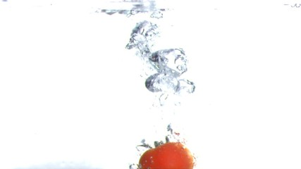 Tomato submerged into water in super slow motion