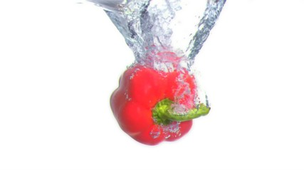 Peppers submerged into water in super slow motion