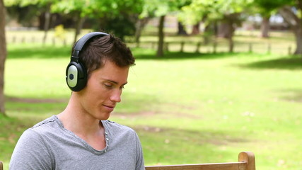 Camera rises to show a man sitting with a laptop while wearing headphones