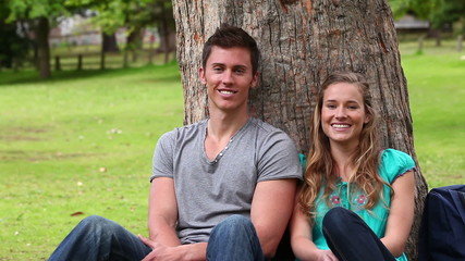 Camera pans as two friends sit against a tree while smiling and looking at the camera