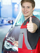 Apprentice for car mechanic in a garage shows thumb up