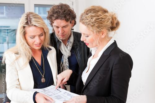 Junge Maklerin erklärt einem Paar einen Mietvertrag