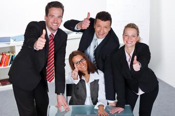 motiviertes mitarbeiterteam zeigt daumen nach oben