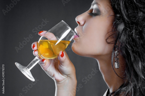 Beautiful girl drink wine on black