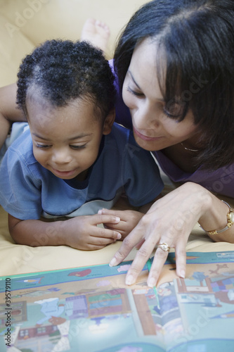 Mother and young son reading book