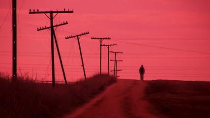 Hombre caminando al atardecer por un camino rural