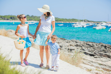 Family of three walking along tropical beach