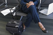 Low section of businesswoman with luggage and laptop