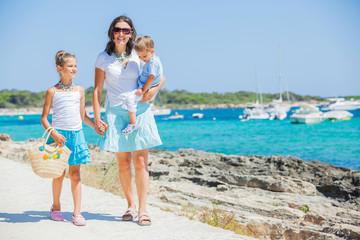 Family of three walking along tropical beach