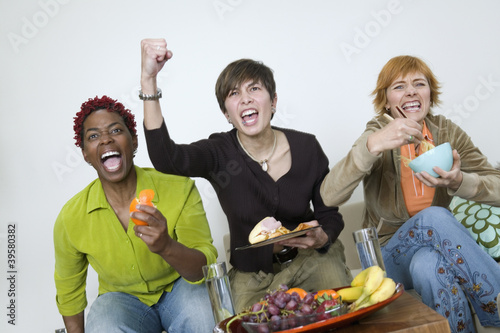 Three women cheering and eating