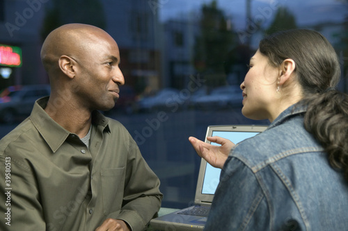 Couple with laptop talking
