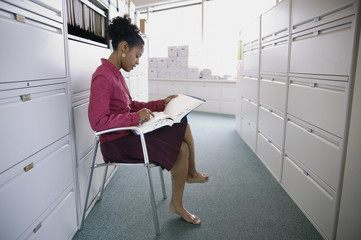 Businesswoman reading files in office