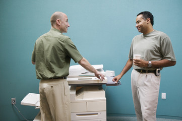 Two businessmen talking at copy machine