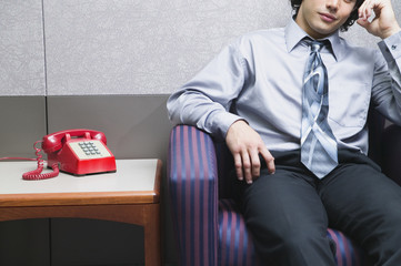Midsection of businessman sitting by phone