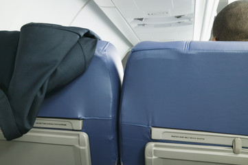 Suit jacket hung over seat on airplane