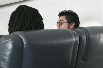 Rear view of two men on airplane