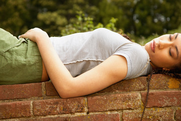 Woman laying on brick wall