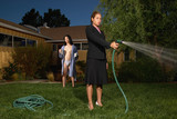 Businesswoman watering yard while husband in robe watches