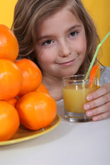 a little blonde girl drinking orange juice