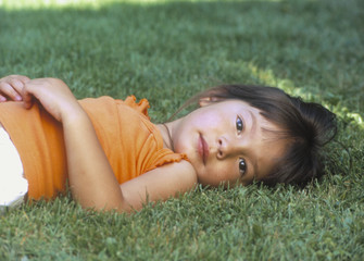 Young girl laying in the grass