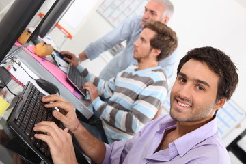 Smiling young man using a computer