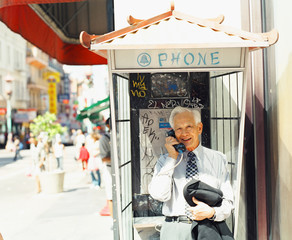 Senior man in phone booth