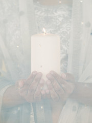 Hazed view of woman holding candle