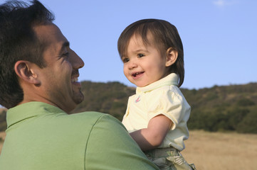 Father and toddler smiling together
