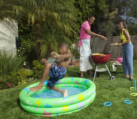Young boy jumping into pool at barbecue