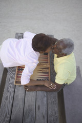 Senior couple kissing over game of backgammon