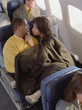 Mature couple cuddling on airplane